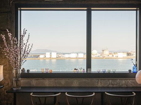 海の見えるカフェ「さろんぶるー」。窓際の席から見えるのは、高松港の倉庫群。